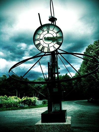 Uhr vor dramatischem Wolkengebilde im Kurpark Oberlaa